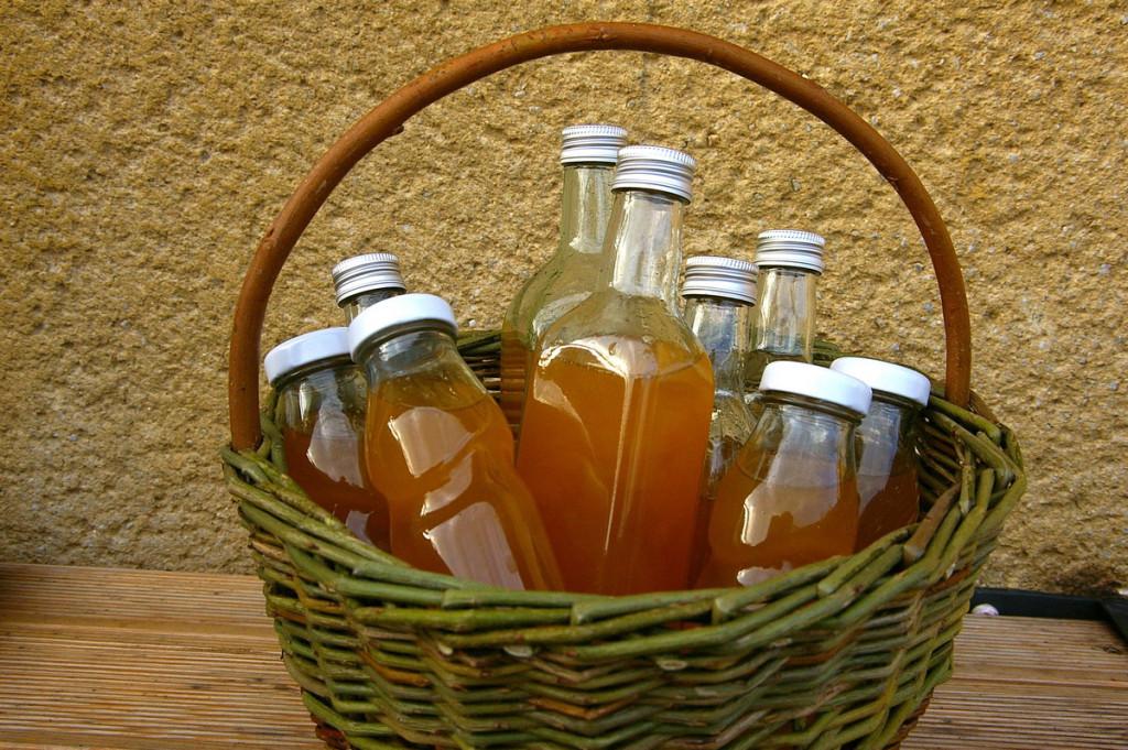 Sirupy v různých lahvích v košíku co pletl kamarád.